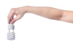 Mão com a lâmpada de poupança de energia no fundo branco Fotografia de Stock