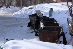 A mão com lixo contra baldes do lixo completos com desperdícios ensaca o transbordamento no pavimento foto de stock royalty free