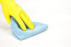 Mão com a luva de borracha que limpa com um pano Imagens de Stock