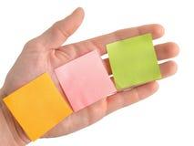 Mão com notas de post-it coloridas vazias Imagens de Stock Royalty Free
