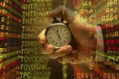 Mão com o cronômetro com fundo do índice de ações Foto de Stock