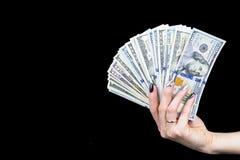 Mão com o dinheiro isolado no fundo preto Dólares americanos disponivéis Punhado do dinheiro Dinheiro de oferecimento da mulher d Imagens de Stock Royalty Free
