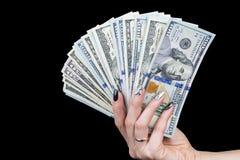 Mão com o dinheiro isolado no fundo preto Dólares americanos disponivéis Punhado do dinheiro Dinheiro de oferecimento da mulher d Fotos de Stock Royalty Free