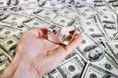 A mão com o navio dos rublos sobre notas de dólar Foto de Stock
