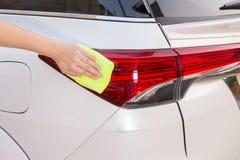 Mão com o pano amarelo do microfiber que limpa a lanterna traseira branca grande c Imagem de Stock Royalty Free