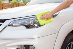 Mão com o pano amarelo do microfiber que limpa o carro branco grande Foto de Stock