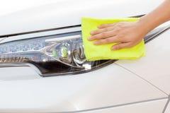 Mão com o pano amarelo do microfiber que limpa o carro branco grande Fotografia de Stock