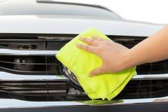 Mão com o pano amarelo do microfiber que limpa o carro branco grande Imagens de Stock