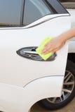 Mão com o pano amarelo do microfiber que limpa o carro branco grande da porta Imagem de Stock
