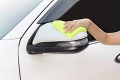 Mão com o pano amarelo do microfiber que limpa o espelho lateral branco grande Imagens de Stock