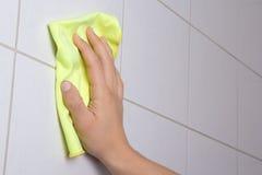 Mão com o pano que limpa as telhas do banheiro Foto de Stock Royalty Free
