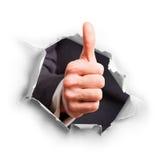 Mão com o polegar que quebra acima através da parede Imagens de Stock