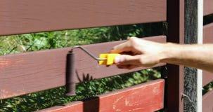 Mão com o rolo de pintura que restaura a cor velha da cerca filme