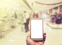 Mão com o smartphone borrado sobre no fundo do shopping Fotografia de Stock Royalty Free