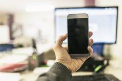 Mão com o smartphone no escritório foto de stock royalty free
