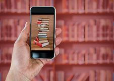 Mão com o telefone que mostra a pilha do livro contra a estante obscura com folha de prova vermelha fotos de stock royalty free