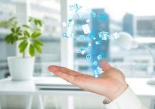 mão com os ícones azuis da aplicação que vêm acima do formulário ele Fundo borrado do escritório Foto de Stock Royalty Free