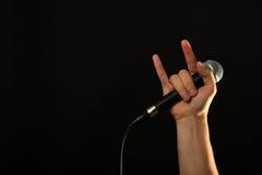 Mão com os chifres do microfone e do diabo isolados no preto Fotos de Stock Royalty Free