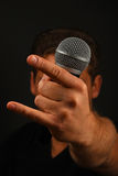 Mão com os chifres do microfone e do diabo isolados no preto Imagens de Stock Royalty Free