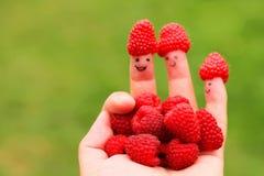 Mão com os dedos felizes que guardam framboesas Imagem de Stock