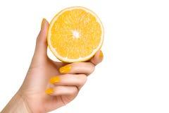 Mão com os pregos amarelos que guardam um fruto do limão Isolado Imagens de Stock Royalty Free