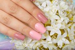 Mão com os pregos manicured artificiais longos coloridos com verniz para as unhas cor-de-rosa fotografia de stock royalty free