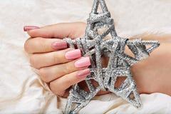 Mão com os pregos manicured cor-de-rosa artificiais longos que guardam um brinquedo de prata do Natal da estrela fotografia de stock