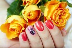 Mão com os pregos manicured curtos coloridos com verniz para as unhas cor-de-rosa e vermelho Imagem de Stock Royalty Free