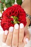A mão com os pregos manicured curtos e a rosa do vermelho floresce Fotografia de Stock