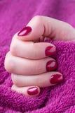 Mão com os pregos manicured curtos vermelhos com uma toalha roxa fotos de stock