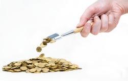 Mão com a pá que strewing moedas na pilha Fotos de Stock Royalty Free