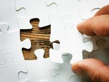 Mão com parte faltante do enigma de serra de vaivém Imagem do conceito do negócio para terminar a parte final do enigma Fotografia de Stock