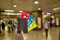 Mão com passaporte vazio e todo o cartão de metro de japão a viajar no Tóquio no fundo borrado do metro imagens de stock royalty free