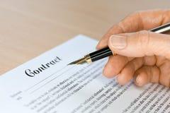 Mão com a pena de fonte que assina um contrato Fotografia de Stock Royalty Free