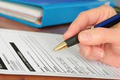 Mão com a pena que termina a informação pessoal no formulário imagem de stock royalty free