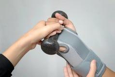 Mão com peso de levantamento do apoio de pulso para o exercício da mão, mão da reabilitação Imagens de Stock