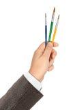 Mão com pincéis coloridos Fotografia de Stock Royalty Free