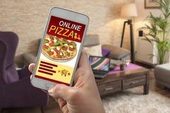Mão com pizza pedindo do smartphone em linha imagens de stock