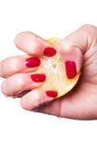 A mão com pregos manicured espreme o limão no branco Imagem de Stock Royalty Free