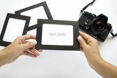 Mão com quadro da foto no fundo da câmera Fotos de Stock Royalty Free