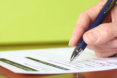 Mão com revestimento protetor de assinatura do verde do close up do formulário da pena Imagens de Stock
