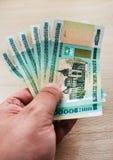 Mão com rublos bielorrussos Fotos de Stock Royalty Free