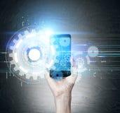 Mão com telefone celular e engrenagens Fotos de Stock