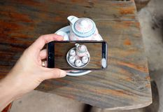 A mão com telefone celular toma uma foto do grupo de copos de chá e de potenciômetro do chá fotografia de stock royalty free