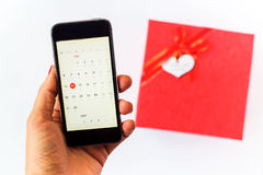 Mão com telefone e a caixa de presente vermelha no backround branco Imagens de Stock Royalty Free
