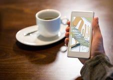 mão com telefone em uma cafetaria Na tela o desaign das escadas novas ao escritório Fotografia de Stock
