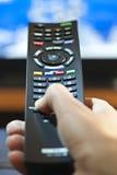 Mão com a televisão de controle remoto Imagem de Stock