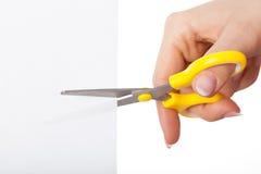 Mão com tesouras amarelas Fotos de Stock Royalty Free