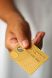 Mão com um cartão de crédito do ouro Imagem de Stock Royalty Free
