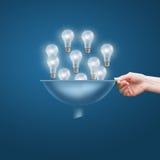 Mão com um funil e muitos bulbos, o conceito dos lotes de ideias do negócio foto de stock royalty free